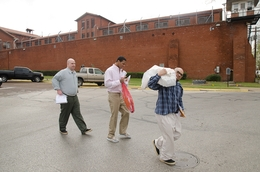 William Crow, Elliott Cornett and Daniel Barraza, all recently released inmates, walk away from the Walls Unit in Huntsville, Texas on March 4, 2011. State legislators are considering halving the $100 given to inmates upon their re-entry to society.