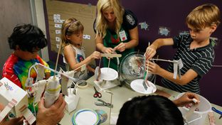 Austin Children's Museum volunteer Alyssa Guiliani helps kids finish their kinetic energy projects at Secret Scientists summer camp in Austin, Texas. Wednesday June 27, 2012.