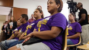 Jessinia Romero, center, listens as clergy joined janitors and supporters during a press conference to express interfaith leaders' support of janitorial workers in Houston, August 2, 2012 in Houston.