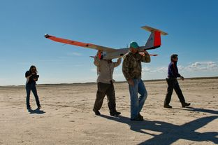 Micheal Cincienne of Absolute Aerospace and Texas A&M Corpus Christi, engineering student Adam Ersepke, and lab coordinator Jack Edward Esparza carry the University's RS-16 unmanned aerial vehicle, otherwise known as a drone, back to the  command center after a test flight over the Kennedy Ranch near Sarita, Texas on January 18, 2013.