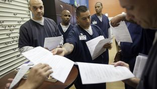An inmate returns tests to his peers during a break from class. Inmates are regularly tested as a part of their academic business curriculum, part of which is modeled on Harvard MBA classes.