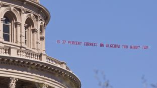 "Airplane buzzed over the Capitol during the lunch hour with banner from the Texas Association of Business asking ""Is 37 % correct on algebra too hard?"""