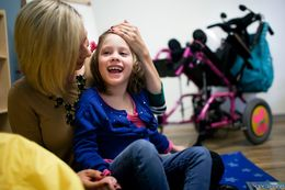 Laura Romero plays with her daughter Brooklyn, who has Cerebral Palsy, during the open house and tour of Seton's new Children's Comprehensive Care Clinic in Austin, Texas.