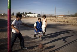 Brothers Angel, left, and Jesus Moreno, middle, and Patrick Cedeño play basketball in the Montana Vista community in far East El Paso, Texas on April 1, 2013. El Paso Electric plans to build a natural gas power plant that will be able to provide electricity to 80,000 homes in the area.