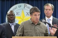 Flanked by Education Commissioner Michael Williams, l, and Lt. Gov. David Dewhurst, Gov. Rick Perry makes a statement on the West, TX disaster on April 18, 2013.
