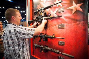 A man who declined to be identified looks at Bushmaster rifles at the NRA's national convention in Houston, Friday May 3, 2013.