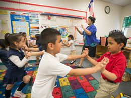 "Pre-K teacher Josefina Pineda teaches her students the concept of ""push"" by having them join hands and push back and forth in her classroom at the Dallas Independent School District elementary school Cesar Chavez Learning Center in Dallas, Texas."