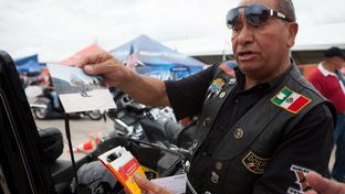 Jorge Rojas Lopez of the Dorados De Villa motorcycle club displays photographs of his fellow riders at the Republic of Texas Biker Rally in Austin, Texas June 14th, 2013.