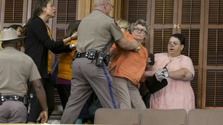 A woman in the Senate gallery pushes back against a police officer and is later arrested during the last hour of the Senate session on June 25, 2013.