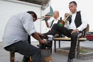 Ignacio Villa, left, and Arturo Ibarra, right, of the mariachi group Los Gavilanes receive shoe shines on Avenida Juárez in Ciudad Juárez, México, Jul. 9, 2013.