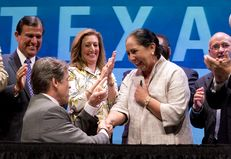 Governor Rick Perry gives one of the pens used to sign the UT merger bill to Dr. Juliet Garcia of UT-Brownsville in a signing ceremony on July 16, 2013.