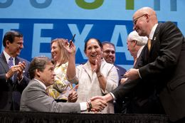 UT-Brownsville President Dr. Juliet Garcia shows off one of the pens that Texas Governor Rick Perry used to ceremonially sign a bill merging two south Texas universities on july 16, 2013.