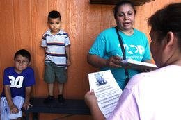 Zoila Chaver, second from right, a member of the Texas Organizing Project giving out information on the coming health care reforms to Dallas resident Graciela Garcia at Garcia's home, Jul. 10, 2013.