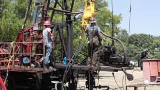 Roughnecks repair a leaking oil well near downtown Kilgore.