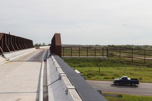 The uncompleted new international railroad bridge near Brownsville passes over the border fence and US 281 before crossing the Rio Grande.