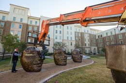 Michael Stutz, a sculptor from San Diego, California, assists members of his team in installing his new creation, Four Faces, at Texas Tech University's Talkington Hall.