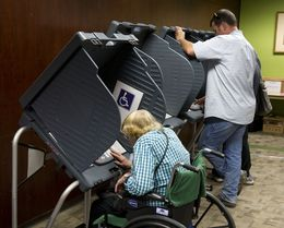 West Austin voters cast ballots in early voting at an Austin Public Library branch on October 30, 2013.