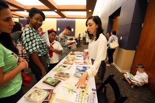Parents look over books and ask questions about curriculum during a parent information session for the new Great Hearts Monte Vista Charter School to open in San Antonio at Temple Beth-El, October 29, 2013.