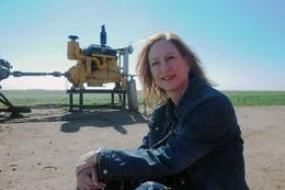 DeDe Cummins sits next to an irrigation well at her farm in the Texas Panhandle.