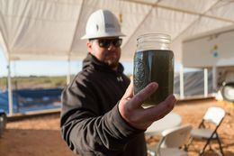 Jonathan Jones, Field Supervisor for Water Rescue Services, holding partially cleaned fracking waste water.