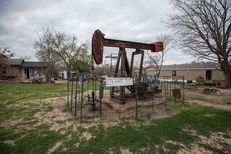 Most of the 183 pump jacks scattered throughout Luling are unadorned, such as this one in the middle a shared yard.