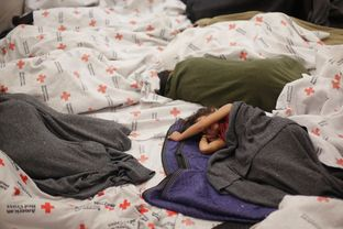 A detainee sleeps in a holding cell at a U.S. Customs and Border Protection processing facility, Wednesday, June 18, 2014, in Brownsville, Texas. CPB provided media tours Tuesday of two locations in Brownsville and Nogales, Ariz. that have been central to processing the more than 47,000 unaccompanied children who have entered the country illegally since Oct. 1.