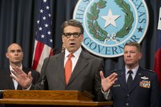 Gov. Rick Perry, flanked by State Rep. Dennis Bonnen, R-Angleton, and Texas Adjutant General John Nichols, announces the deployment of National Guard troops to the Texas border on July 21, 2014.