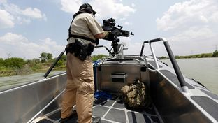 A Texas Parks and Wildlife Warden stands next to a 30 caliber rifle as he patrols the Rio Grand on the U.S.-Mexico border , Thursday, July 24, 2014, in Mission, Texas. Texas is spending $1.3 million a week for a bigger DPS presence along the border.