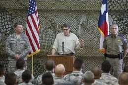 Texas Governor Rick Perry, flaned by Adjutant General John Nichols, l, and DPS Director Steve McCraw, talks to National Guard troops at Camp Swift on August 13, 2014.