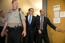 Governor Rick Perry is led into the booking area of the Travis County Courthouse for fingerprints and photographs on August 19, 2014.