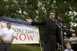 Former New Hampshire Gov. John Sununu looks on as Gov. Rick Perry speaks at a Stratham rally on Saturday.