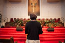 A woman, who asked not to be identified because she fears for her safety, stands near the pulpit at the end of service at First Baptist Church on Sunday, Sept. 14, 2014, in El Paso. The woman fled Boko Haram in Nigeria and is now seeking asylum.