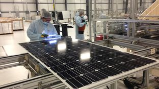 A worker at Mission Solar in San Antonio inspects the protective coating of a fully assembled solar panel for bubbles that could hinder efficiency. The company runs Texas' biggest solar panel manufacturing plant.