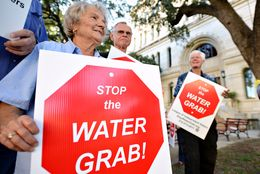 Lee County resident Hilde Sides protests the Vista Ridge Water Supply Project with other Lee and Bastrop County residents outside the San Antonio City Council public hearing on the project on Oct. 8.