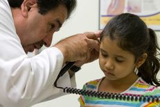 "Dr. Javier Saenz checks the ear of Viviana Escareño, 6, for infection. The young girl's mother, Claudia Escareño, has brought ""Vivi"" to Saenz's clinic since she was born."