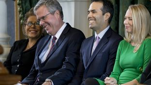 Jeb Bush puts his hand on his son George P. Bush's knee during a light moment in the younger Bush's swearing-in ceremony on Jan. 2, 2015, as Texas land commissioner. At right is George P. Bush's wife, Amanda Bush.