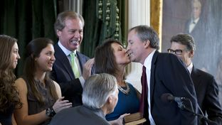 Attorney General Ken Paxton gets a kiss from his wife, Angela, after he was sworn in on Jan. 5, 2015, in the Texas Senate chamber.