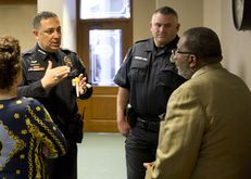 Austin police Chief Art Acevedo and Austin Police Association President Kenneth Casaday speak with Sen. Royce West D-Dallas on Feb. 12th, 2015 inside Texas Capitol as the Senate Committee on State Affairs listens testimony on SB 11 & SB 17.