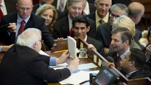 House Parliamentarian Chris Griesel shows the rule book to a group of House members including Rep. David Simpson, R-Longview, during a point of order called on HB 11 March 18, 2015.