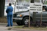 A BP employee stands near a safety sign during a BP memorial service inside the plant in Texas City for the employees that were injured and killed in the BP plant explosion in Texas City,Texas January 30, 2005.