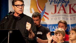 Rick Perry speaks to an audience of veterans and supporters at a fundraiser for the Puppy Jake Foundation, which trains service dogs for wounded war veterans, at Hotel Pattee in Perry, Iowa, on June 6, 2015. Following the fundraising event, Perry led a motorcycle ride for veterans from Perry to Boone, Iowa, where he spoke at U.S. Sen. Joni Ernst's Roast and Ride.
