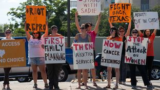 Abortion rights activists protest across from the governor's mansion in Austin on June 9, 2015.