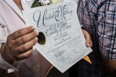Pamela Holwerds holds up her marriage license following the ceremony that married over 40 same-sex couples on the south lawn of the Texas State Capitol in Austin on July 4, 2015. (Tamir Kalifa for The Texas Tribune)
