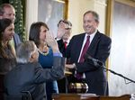 Attorney General Ken Paxton, surrounded by family, takes the oath of office in the Senate chamber on January 5, 2015.