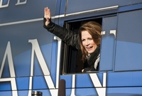 Republican candidate Michele Bachmann waves to reporters from her bus after leaving the Rock the Caucus event at Valley High School in Des Moines on January 3, 2012.