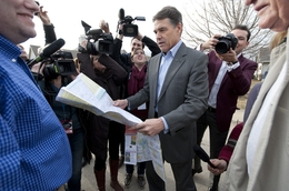 Gov. Rick Perry unfolding a Texas map on Dec. 31, 2011, to show Des Moines residents where his hometown of Paint Creek is located.