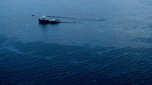 Response boats work to clean up oil where the Deepwater Horizon offshore oil rig sank on April 22, 2010.