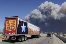 "A grocery truck with the Texas ""Lone Star"" drives east on Texas 71 toward the wildfire east of Bastrop that is burning out of control on September 5, 2011."
