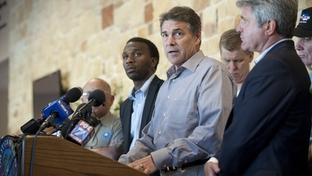 Texas Gov. Rick Perry, c,  answers question from citizens and the media in Bastrop after his return from a campaign trip to South Carolina on September 5, 2011.