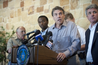 A tired-looking Gov. Rick Perry listens to a reporter's question at the Bastrop Civic Center during a press conference on the wildfires on September 5, 2011.
